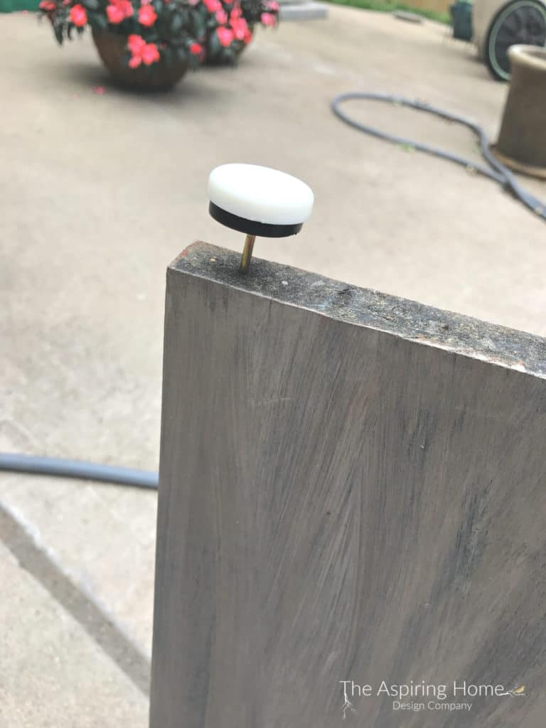 Add Button feet to base of the DIY outdoor stone entry table