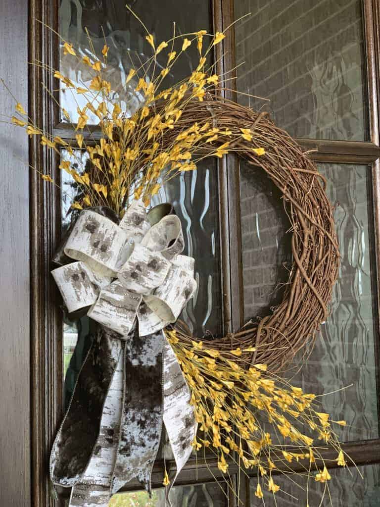 fall grapevine wreath with yellow flowers hanging on front door